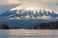 Kayaker paddles the waters of Sitka Sound, view of inactive volcano, Mount Edgecumbe on Kruzof island, southeast, Alaska.