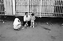 A father and his children drinking a cup of tea in front of the Bazaar. Tehran, Iran, 2007