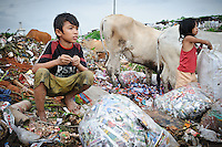 Ashuar, 12, and Sida, 8, searching through bags of discarded waste at the 'Traah mountain', Makassar, Sulawesi, Indonesia.
