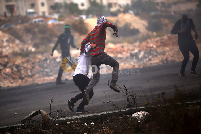 Palestinian protesters take part in clashes with Israeli security forces near the Jewish settlement of Beit El, near the West Bank city of Ramallah October 26, 2015. Israeli Prime Minister Benjamin Netanyahu has raised the possibility of revoking benefits and travel rights of some Palestinians living in East Jerusalem, a government official said on Monday, in response to a wave of Palestinian violence. Photo by Shadi Hatem