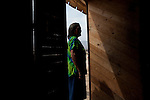 A woman looks out of her house on Monday, Apr. 13, 2009 in Ventanilla, Peru.