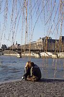 Lovers, Ile de la Cité, river Seine with the passerelle des Arts and the Louvre Museum in the distance, Paris, France Picture by Manuel Cohen
