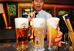 A barman serves up glasses of draft beer made by Sapporo Breweries Ltd. at Sapporo Beer Station in Tokyo, Japan