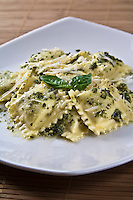 Ravioli pasta on a white plate with a sauce of grated romano cheese, basil  pesto and a sprig of basil as a garnish.