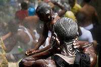 A Haitian boy soaps his head in the waterfall during the annual religious pilgrimage in Saut d'Eau, Haiti, July 16, 2008. Every year in summer thousands of pilgrims from all over Haiti make the religious journey to the Saut d'Eau waterfall (100km north of Port-au-Prince). It is believed that 150 years ago the spirit of Virgin Mary (Our Lady of Mount Carmel) has appeared on a palm tree close to the waterfall. This place became a main pilgrimage site in Haiti since then. Haitians wearing only underwear perform a bathing and cleaning ritual under the 100-foot-high waterfall. Voodoo followers (many Haitians practise both voodoo and catholicism) hope that Erzulie Dantor, the Voodoo spirit of water, manifest itself and they get possessed for a short moment, touched by her presence.