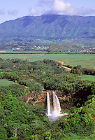 Wailua Falls and Mt. Waialeale, east Kauai, with misty waterfall rainbow, aerial photo.