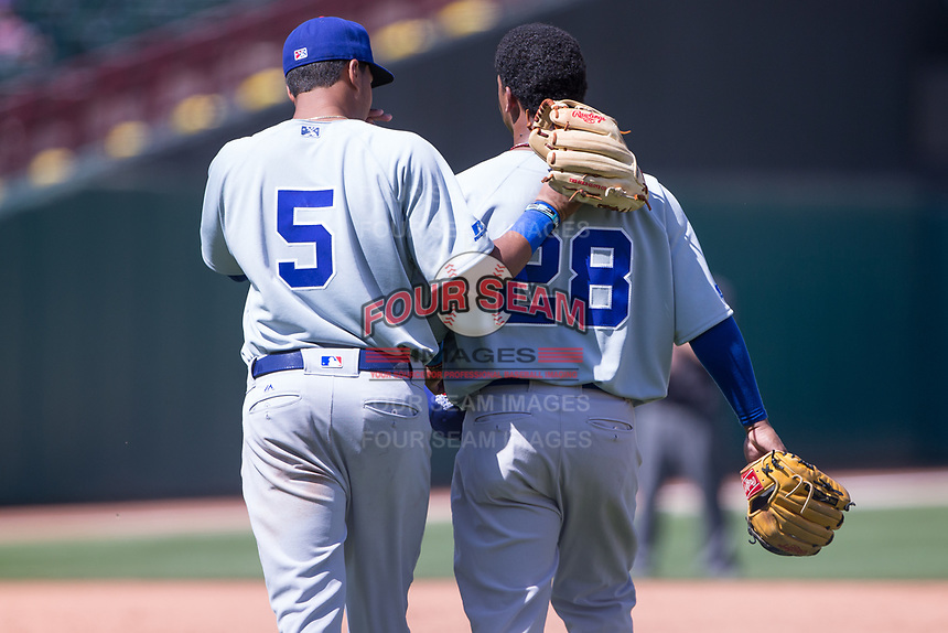 Jeimer Candelario (5) and Ozzie Martinez (28) of the Iowa Cubs talk as they take the field in a game against the Oklahoma City Dodgers at Chickasaw Bricktown Ballpark on April 9, 2016 in Oklahoma City, Oklahoma.  Oklahoma City defeated Iowa 12-1 (William Purnell/Four Seam Images)