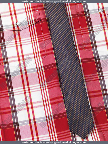 Closeup of a fancy mens red tartan shirt with a slim stripy necktie