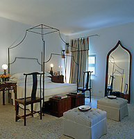 Simple iron-framed bed in a room furnished with Chinese sidetables, chairs and lacquer boxes