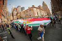 Marchers with a giant Iranian flag at the 11th annual Persian Parade on Madison Ave. in New York on Sunday, April 13, 2014. The parade celebrates Nowruz, New Year in the Farsi language. The holiday symbolizes the purification of the soul and dates back to the pre-Islamic religion of Zoroastrianism. (© Richard B. Levine)