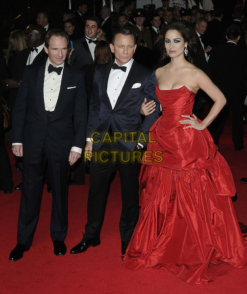 Ralph Fiennes, Daniel Craig, Berenice Marlohe.'Skyfall' Royal World Film Premiere, Royal Albert Hall, Kensington Gore, London, England..23rd October 2012.full length black strapless dress cleavage gathered hands on hips red tuxedo white shirt bow tie.CAP/CAN.©Can Nguyen/Capital Pictures.