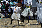 A small boy, part of a liturgical dance group, performs during an outdoor Mass in Christ the King Catholic parish in Malakal, Southern Sudan, on November 21, 2010.