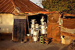 The Gambia. Shiny aluminium pots and pans on sale from a falling down shed.
