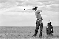cowboy golfing in a field in New Mexico