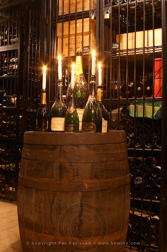 Wire cages with private wine collections and a standing barrel with empty bottles and a candle at the wine cellar storage company Grappe in Stockholm where private individual s can store and age wine bottles. Källaren Grappe Wine Storage Cellar, Stockholm, Sweden, Sverige, Europe