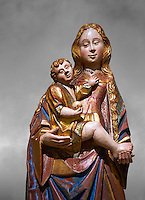Gothic statue of The Virgin Mary (Madonna) holding the baby Jesus. Polychrome and gold leaf on wood by the Circle of Gil de Siloe around 1500, probably from Castella. Inv MNAC 64028. National Museum of Catalan Art (MNAC), Barcelona, Spain. Against a grey art background.