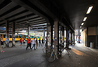 Underneath the train bridge in Alexanderplatz, with an U-Bahn passing and people milling around, Berlin, Germany. Picture by Manuel Cohen