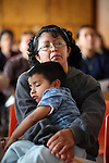 A mother craddles her child while attending a meetign in a Mexico City's school, October 3, 2008. Photo by Heriberto Rodriguez