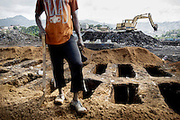 A grave digger at the King Tom cemetery near a group of pre-dug graves. Due to the rapid increase in burials, caused by the ebola crisis, the cemetery is being enlarged and parts of a nearby rubbish dump is also being used to bury the dead.