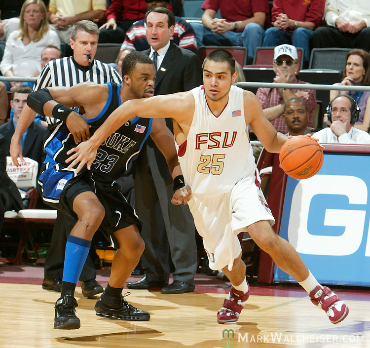 While Duke Blue Devil coach Mike Krzyzewski (rear) looks on, Florida State's Diego Romero (25) tries to get around Duke's forward Shelden Williams (23) in Tallahassee, Florida  March 1, 2006.  Florida State upset the number one ranked Duke Blue Devils 79-74.