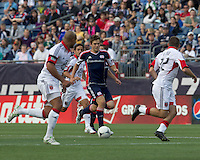 New England Revolution midfielder Kelyn Rowe (11) brings the ball forward. In a Major League Soccer (MLS) match, DC United defeated the New England Revolution, 2-1, at Gillette Stadium on April 14, 2012.
