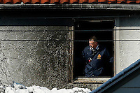 NYFD officer watches from the window in the second floor where at least 7 children died during the fire in Brooklyn, New York. 21.03.2015. Eduardo Munoz Alvarez/VIEWpress.
