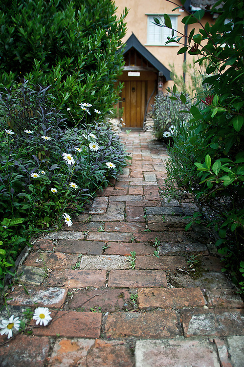 Old path made of bricks leading to cottage door