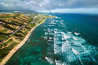 An aerial of rows of waves rolling towards shore along Diamond Head Crater, with the coastline of East O'ahu continuing to Koko Crater and Koko Head.