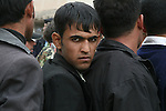 A young man waits to apply for a job as a police officer in Kirkuk, Iraq. Officials sought to fill 1,300 slots for the next training class, but were overwhelmed when more than 4,000 applicants showed up. More than half were turned away at the gate, and hundreds of others waited in line for hours, but never got a chance to submit their papers. The event was shut down after a U.S. advisor observed an Iraqi recruiting officer take a bribe from an applicant. Dec. 6,  2007. DREW BROWN/STARS AND STRIPES