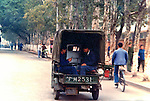 Two men dressed in blue traveling in the back of a truck. Pictures taken in Canton China in 1977 at the time of the cultural revolution.