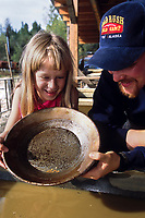 A young girl gets help panning for gold in Fairbanks, Alaska.