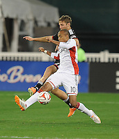 Washington D.C. - April 5, 2014: Teal Bunbury from the New England Revolution shields the ball against Jeff Parke  of D.C. United.  D.C. United defeated 2-0 the New England Revolution during a Major League Soccer match for the 2014 season at RFK Stadium.