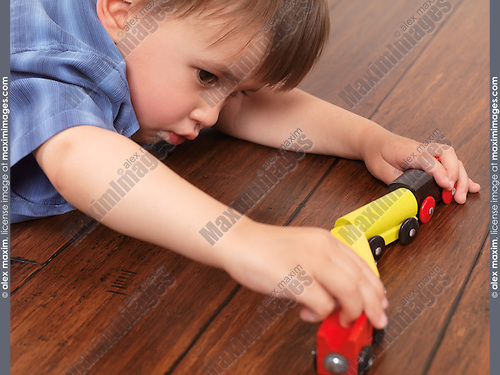 Two year old boy playing with a toy train lying on hardwood floor