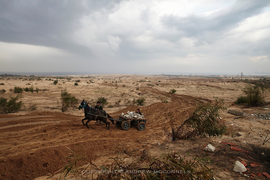 Boys force a horse and cart laden with rubble along a track made by an Israeli tank in Gaza's northern buffer zone with Israel. The buffer zone is 300 meter wide stretch of land in which dozens have been maimed and killed by Israeli snipers.