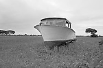 A workboat being repaired in a field beside a house is a common sight on Harkers Island.  Boatbuilders prided themselves on being &quot;backyard&quot; boatbuilders.  When she was finished, the boat was moved to the shoreline and launched.
