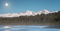 Full moon in blue hour at Gillespies Beach with winter views of Mt. Tasman (left) 3497m and Aoraki Mt. Cook (right) 3724m, two highest New Zealand mountains, Westland Tai Poutini National Park, West Coast, UNESCO World Heritage Area, New Zealand, NZ