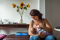 A young woman breastfeeds her baby in her living room at home.<br /> <br /> 10/09/12<br /> Berkshire, England, UK