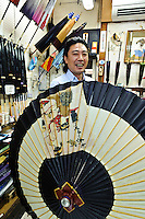 Michihiko Sugahara holding a parasol in his shop, Asakusa, Tokyo, Japan, August 28, 2011. Sensoji is one of the oldest temples in Tokyo, and the shopping arcades around it have sold visitors souvenirs for centuries.