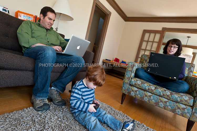 """4/23/2011--Seattle, WA, USA..Brad Kahn, 40, his wife Erin Kahn, 38 and their son Ezra, 2, in their home in Seattle, WA, checking email on their laptops while Ezra plays games on an an old iPhone 3 that Mr. Kahn no longer uses. Mr. Kahn, an environmental consultant in Seattle, said he often communicates with wife, Erin, by e-mail, even when the two are sitting a few feet apart on the sofa, tapping away on their laptops. He will cut her off if she starts instructing him verbally about what he calls his 'honey-do' list of chores for the weekend, he said, and ask her to send it electronically. It's simply more efficient, Mr. Kahn, 40, explained: """"If I misunderstood any directions, having a written record can be very useful in maintaining marital bliss."""" ..©2001 Stuart Isett. All rights reserved."""