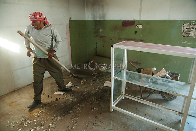 13/11/2015-- Iraq,Sinjar -- a Yizidian man is cleaning his store which was a store for selling alcoholic beverages before Sinjar was taken by ISIS, he wants to go back to his job after the liberation of Sinjar.