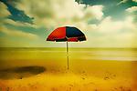 An umbrella standing on a sandy beach