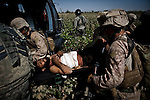 "10/7/2010 Marjah, Helmand Province, Afghanistan.US Marines load a wounded Afghan man onto a US Army Medevac helicopter in Marjah, Helmand Province, Afghanistan. ..The Helicopter Medevac teams of Task Force Destiny, based at Forward Operating Base Dwyer in Afghanistan's war-torn Helmand Province have a tough job. Servicing a large area that includes still restive southern Marjah, and much of the Helmand River Valley, TF Destiny answers the call to transport gravely wounded US Marines and Afghan civilians from the point of injury in the field to Role 3 trauma centers on bases in the area--often times landing under fire to extract Marines and soldiers that would otherwise succumb to their wounds. After the Medevac helicopter and it's ""chase"" UH-60 Blackhawk companion aircraft get a call, they can be on the ground picking up a patient in as little as 20 minutes--delivering the fallen to a surgical theater within what flight medics refer to as ""the golden hour""--or the hour after a catastrophic injury during which a patients transfer from basic battlefield triage care to a modern trauma surgical unit can mean the difference between life and death. ."