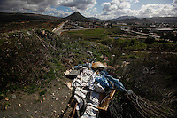 Hundreds of would-be migrants live in squalid makeshift camps along the canyons that overlook the border with the United States. Many of them have been deported multiple times and, because of the vacancy limits on some of the immigrant shelters in these border cities, many of them end up homeless and living in squalid camps while they attempt to cross the border...Tecate, Baja California, Mexico - February 8, 2013.  (Javier Manzano / For The Washington Post).