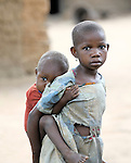 A girl cares for her younger sibling in the Congolese village of Minga.