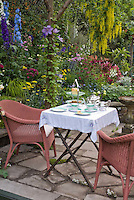 Eating outdoors with wicker chairs, tea set, lush garden, stone patio