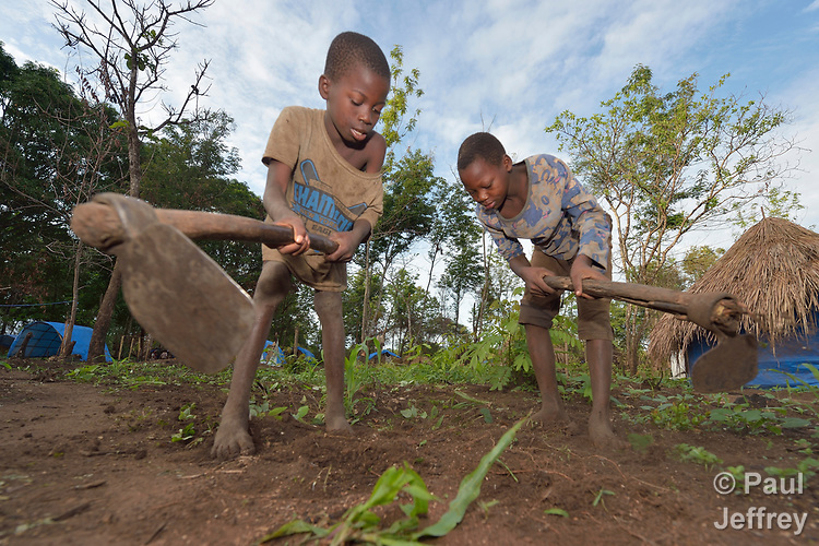A boy and girl prepare the soil for planting in a camp for for than 5,000 displaced people in Riimenze, in South Sudan's Gbudwe State, what was formerly Western Equatoria. Families here were displaced at the beginning of 2017, as fighting between government soldiers and rebels escalated.<br /> <br /> Two Catholic groups, Caritas Austria and Solidarity with South Sudan, have played key roles in assuring that the displaced families here have food, shelter and water.<br /> The camp formed around the Catholic Church in Riimenze as people fled violence in nearby villages for what they perceived as the safety offered by the church.