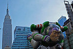 People take part of the annual Thanksgiving day parade with a Buzz's balloon as the Empire State Building is seen on the skyline in New York, November 22, 2012. . Photo by Eduardo Munoz Alvarez / VIEWpress.