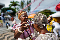 A Baiana woman performs the 'popcorn bath', an Afro-Brazilian spiritual cleansing ritual, in front of the St. Lazarus church in Salvador, Bahia, Brazil, 30 January 2012. Every year on the last Sunday of January, the religious festival of Saint Lazarus takes place on a hill where the chapel of the same name was built in the 18th century. Faithful, of both the Catholic and Candomblé religions, dressed in the traditional white, usually undergo a purification cleansing ritual (banho de pipoca). As both Saint Lazarus and Omolú are related to diseases and healing, followers bring votive objects made of wax as a demonstration of gratitude and faith. The celebration ends with the festive Catholic Mass during which the elements of African mythology are present.