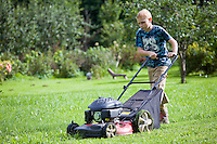 Teenage Boy Mowing Lawn Using Lawn Mower