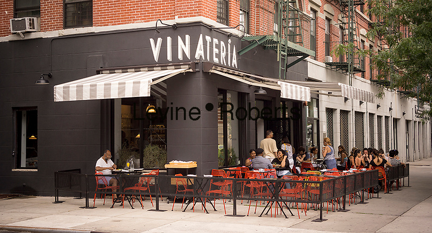 Patrons sit at the outdoor cafe of the Vinateria restaurant on Frederick Douglass Blvd in the neighborhood of Harlem in New York on Sunday, July 13, 2014. Wide sidewalks and a renaissance in Harlem have caused a number of restaurants to open catering to the more upwardly mobile newer residents. (© Richard B. Levine)